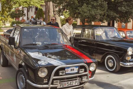 old timer: NOVIGRAD CROATIA  SEPTEMBER 13 2014: Unrecognizable people look around vintage cars on 5th International Old Timer Car Rally. The event organized by the old timer club Eppur si muove from Umag.