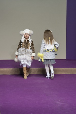 children's show: KIEV UKRAINE  AUGUST 28 2014: Association of Childrens Fashion little girl models walks the runway at Kyiv Fashion 2014 show in KyivExpoPlaza exhibition center. It was the 27th edition of the popular Kyiv Fashion International Vogue Festival.
