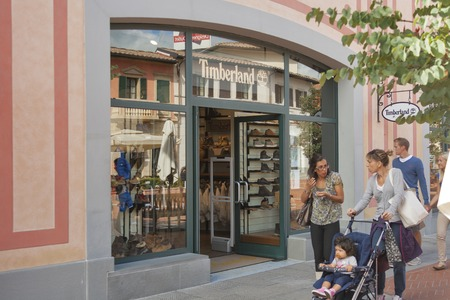 timberland: MUGELLO ITALY  SEPTEMBER 11 2014: People walk along Timberland store in McArthurGlen Designer Outlet Barberino situated in 30 minutes from Florence. McArthurGlen Group opened its first designer outlet in 1995. It has 20 designer outlets in the UK and Cont