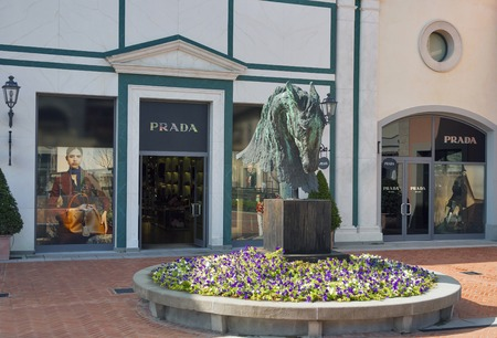 prada: MUGELLO ITALY  SEPTEMBER 11 2014: Facade of Prada store in McArthurGlen Designer Outlet Barberino situated in 30 minutes from Florence. Prada is an Italian luxury fashion house specializing in leather and fashion accessories shoes luggage perfumes watches