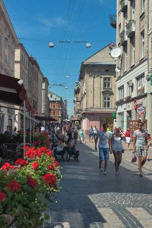 mention: LVIV, UKRAINE - JULY 29, 2014: People walk along pedestrian Galician street with cafe and small shops. The first mention of the street dates back to 1382 and till now its name remains unchanged.