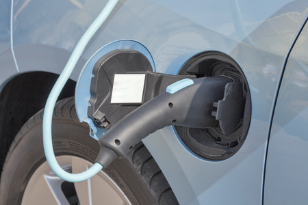 plugged in: Charging an electric car with the power cable supply plugged in, closeup