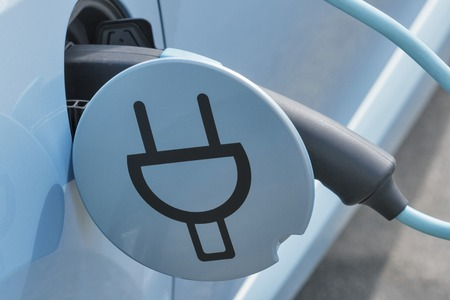 Charging an electric car with the power cable supply plugged in, closeup
