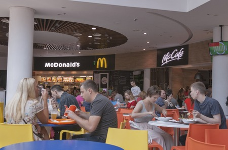 KIEV, UKRAINE - JULY 19, 2015: Unrecognizable people eating in a food court of Ocean Plaza biggest in Ukraine shopping mall with total area of 160.000 square meters, about 400 shops and 30 restaurants