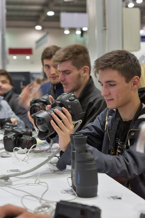 fish eye lens: KIEV, UKRAINE - OCTOBER 11, 2015: Visitors testing professional photographic cameras on Canon booth during CEE 2015, the largest electronics trade show of Ukraine in ExpoPlaza Exhibition Center. Editorial