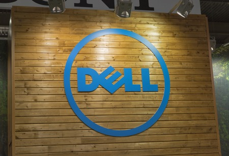 hall monitors: KIEV, UKRAINE - OCTOBER 11, 2015:  Dell logo on a wooden base illuminated by searchlights on company booth during CEE 2015, largest electronics trade show of Ukraine in ExpoPlaza Exhibition Center.