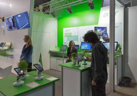 hall monitors: KIEV, UKRAINE - OCTOBER 11, 2015: People visit Acer, a Taiwan based international computer company booth during CEE 2015, the largest electronics trade show of Ukraine in ExpoPlaza Exhibition Center.
