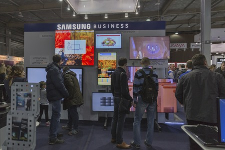 hall monitors: KIEV, UKRAINE - OCTOBER 11, 2015: People visit Samsung, South Korean electronics manufacturer company booth during CEE 2015, largest electronics trade show of Ukraine in ExpoPlaza Exhibition Center