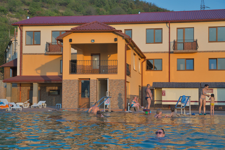 salinity: BEREHOVE, UKRAINE - SEPTEMBER 02,2015: Unrecognizable people swim in outdoor thermal spa pool Zhayvoronok. Berehove city became famous for its unique thermal healing waters of high salinity.