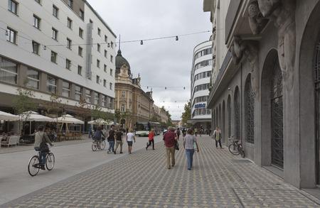 old buildings: LJUBLJANA, SLOVENIA - SEPTEMBER 04, 2015: Unrecognizable pedestrians walk along central Slovenska Street in front of Hotel Slon and Central Post. Ljubljana is the biggest city and the capital of Slovenia.