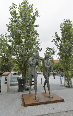 expulsion: LJUBLJANA, SLOVENIA - SEPTEMBER 04, 2015: Modern sculpture of Adam and Eve, ashamed and banished from Paradise, made by contemporary Slovene sculptor Jakov Brdar. Editorial