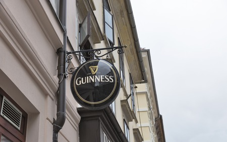 originated: LJUBLJANA, SLOVENIA - SEPTEMBER 04, 2015: Guinness logo on a city street building facade. Guinness is an Irish dry stout that originated in the brewery of Arthur Guinness at St. James Gate, Dublin, Ireland in 1759.