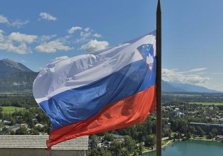 fluttering: Slovenian national flag fluttering over Lake Bled and town Stock Photo