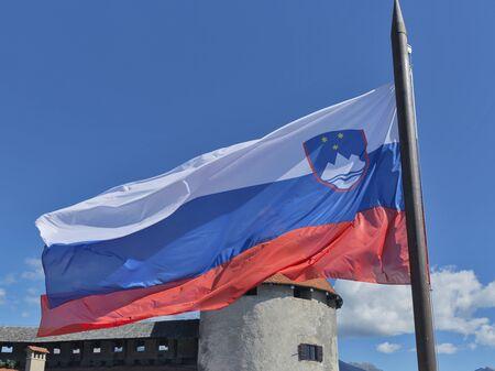 fluttering: Slovenian national flag fluttering over Bled Castle