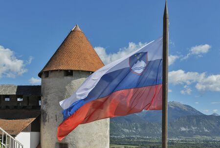 slovenian: Slovenian national flag fluttering over Bled Castle