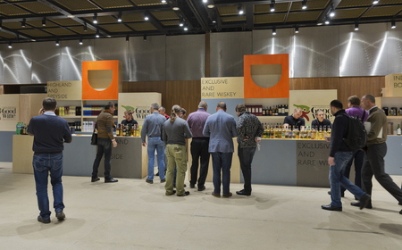 dram: KIEV, UKRAINE - NOVEMBER 21, 2015: Unrecognized people visit Good Wine Exclusive and Rare Single Malt Scotch Whiskey boothes at 1st Ukrainian Whisky Dram Festival in Parkovy Exhibition Center.