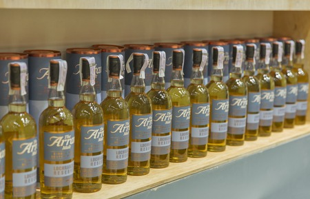 dram: KIEV, UKRAINE - NOVEMBER 21, 2015: The Arran Lochranza Reserve Single Malt Scotch Whisky bottles closeup in a row for tasting on booth at Ukrainian Whisky Dram Festival in Parkovy Exhibition Center.
