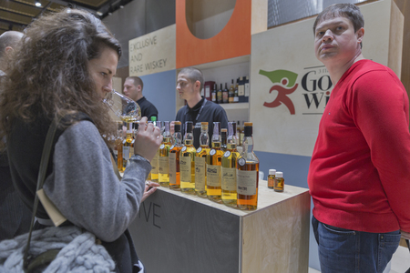 dram: KIEV, UKRAINE - NOVEMBER 21, 2015: Unrecognized people visit Good Wine Exclusive and Rare Single Malt Scotch Whiskey booth at 1st Ukrainian Whisky Dram Festival in Parkovy Exhibition Center. Editorial