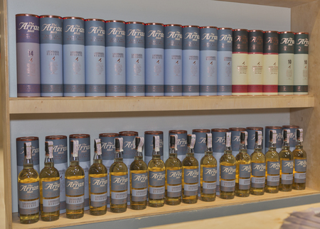 dram: KIEV, UKRAINE - NOVEMBER 21, 2015: The Arran Lochranza Reserve and others Single Malt Scotch Whisky bottles closeup in a row for tasting on booth at Whisky Dram Festival in Parkovy Exhibition Center.