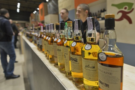 dram: KIEV, UKRAINE - NOVEMBER 21, 2015: Unrecognized presenters work on Good Wine Exclusive and Rare Single Malt Scotch Whiskey booth at 1st Ukrainian Whisky Dram Festival in Parkovy Exhibition Center.