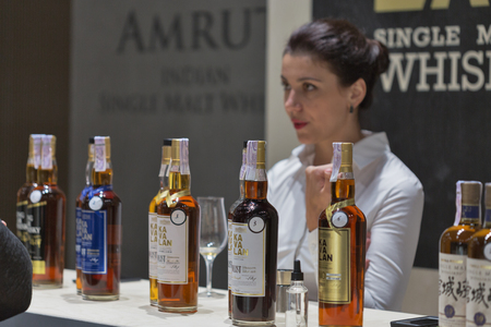 dram: KIEV, UKRAINE - NOVEMBER 21, 2015: Unrecognized woman sommelier works on Asian distilleries of Single Malt Scotch Whisky booth at 1st Ukrainian Whisky Dram Festival in Parkovy Exhibition Center.