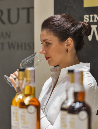 unrecognized: KIEV, UKRAINE - NOVEMBER 21, 2015: Unrecognized woman sommelier works on Asian distilleries of Single Malt Scotch Whisky booth at 1st Ukrainian Whisky Dram Festival in Parkovy Exhibition Center.