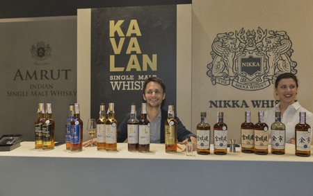 sommeliers: KIEV, UKRAINE - NOVEMBER 21, 2015: Unrecognized sommeliers work on Asian distilleries of Single Malt Scotch Whisky booth at 1st Ukrainian Whisky Dram Festival in Parkovy Exhibition Center.
