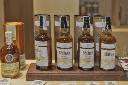 dram: KIEV, UKRAINE - NOVEMBER 21, 2015: BenRiach and Bruichladdich Single Malt Scotch Whisky bottles closeup in a row for tasting on booth at 1st Ukrainian Whisky Dram Festival in Parkovy Exhibition Center