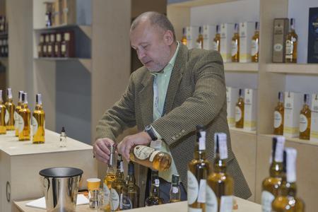 sommelier: KIEV, UKRAINE - NOVEMBER 21, 2015: Unrecognized sommelier works on Glen Grant Speyside  Single Malt Scotch Whisky distillery booth at 1st Ukrainian Whisky Dram Festival in Parkovy Exhibition Center. Editorial