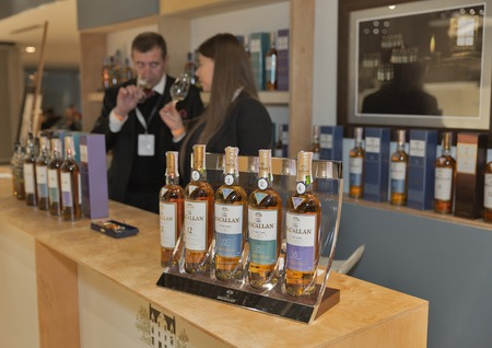 scotch whisky: KIEV, UKRAINE - NOVEMBER 21, 2015: Unrecognized presenters work on The Macallan Single Malt Scotch Whisky distillery booth at 1st Ukrainian Whisky Dram Festival in Parkovy Exhibition Center. Editorial