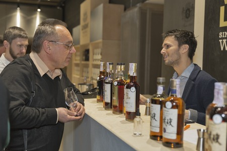 dram: KIEV, UKRAINE - NOVEMBER 21, 2015: Unrecognized people visit Asian distilleries of Single Malt Scotch Whisky booth at 1st Ukrainian Whisky Dram Festival in Parkovy Exhibition Center.