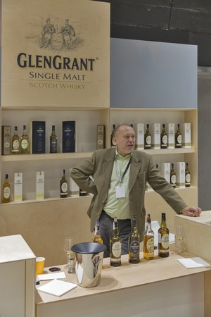unrecognized: KIEV, UKRAINE - NOVEMBER 21, 2015: Unrecognized sommelier works on Glen Grant Speyside  Single Malt Scotch Whisky distillery booth at 1st Ukrainian Whisky Dram Festival in Parkovy Exhibition Center. Editorial