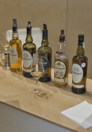 dram: KIEV, UKRAINE - NOVEMBER 21, 2015: Various kinds of Glen Grant Speyside Single Malt Scotch Whisky bottles closeup in a row for tasting on booth at 1st Whisky Dram Festival in Parkovy Exhibition Center