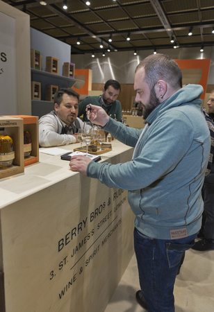 dilute: KIEV, UKRAINE - NOVEMBER 21, 2015: Unrecognized people visit The Glenrothes Speyside Single Malt Scotch Whisky distillery booth at 1st Ukrainian Whisky Dram Festival in Parkovy Exhibition Center. Editorial