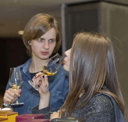 unrecognized: KIEV, UKRAINE - NOVEMBER 21, 2015: Unrecognized young visitors taste sample of Single Malt Scotch Whisky at 1st Ukrainian Whisky Dram Festival in Parkovy Exhibition Center.