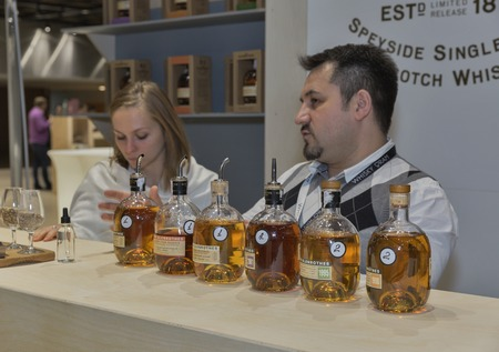 unrecognized: KIEV, UKRAINE - NOVEMBER 21, 2015: Unrecognized presenters work on The Glenrothes Speyside Single Malt Scotch Whisky distillery booth at 1st Ukrainian Whisky Dram Festival in Parkovy Exhibition Center. Editorial