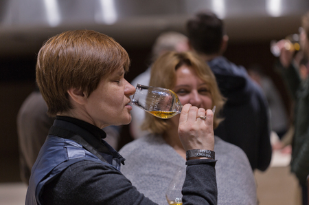 scotch whisky: KIEV, UKRAINE - NOVEMBER 21, 2015: Unrecognized middle age visitor taste sample of Single Malt Scotch Whisky at 1st Ukrainian Whisky Dram Festival in Parkovy Exhibition Center.