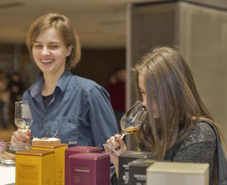 liquor girl: KIEV, UKRAINE - NOVEMBER 21, 2015: Unrecognized young visitors taste sample of Single Malt Scotch Whisky at 1st Ukrainian Whisky Dram Festival in Parkovy Exhibition Center.