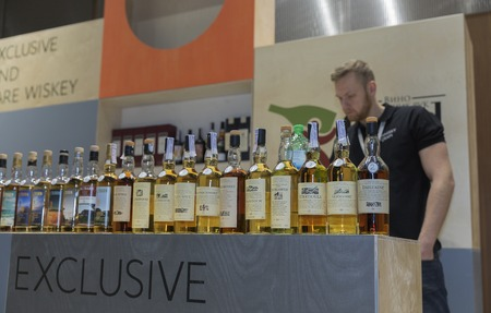dram: KIEV, UKRAINE - NOVEMBER 21, 2015: Unrecognized presenter works on Good Wine Exclusive and Rare Single Malt Scotch Whiskey booth at 1st Ukrainian Whisky Dram Festival in Parkovy Exhibition Center. Editorial