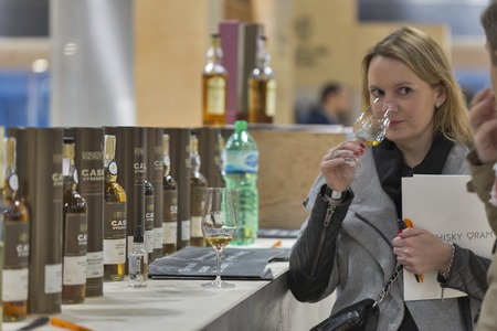 unrecognized: KIEV, UKRAINE - NOVEMBER 21, 2015: Unrecognized woman taste Single Malt Scotch Whisky on Gordon and MacPhail booth at 1st Ukrainian Whisky Dram Festival in Parkovy Exhibition Center.