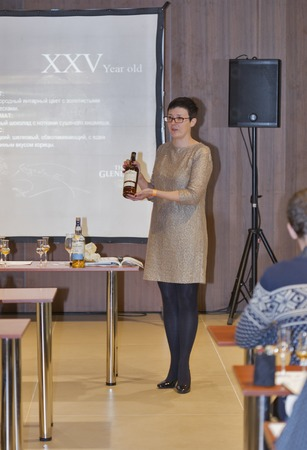 dram: KIEV, UKRAINE - NOVEMBER 21, 2015: Unrecognized woman presenter provide corporate presentation of The Glenlivet Single Malt Scotch Whiskey at 1st Whisky Dram Festival in Parkovy Exhibition Center. Editorial