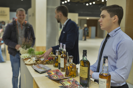 dram: KIEV, UKRAINE - NOVEMBER 21, 2015: Unrecognized presenters work on Speyside and Skye Single Malt Scotch Whisky booth at 1st Ukrainian Whisky Dram Festival in Parkovy Exhibition Center.