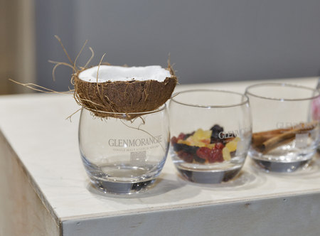 dram: KIEV, UKRAINE - NOVEMBER 21, 2015: Composition with glasses, coconut, fruits and cinnamon at Glenmorangie Single Malt Scotch Whisky booth at 1st Whisky Dram Festival in Parkovy Exhibition Center.