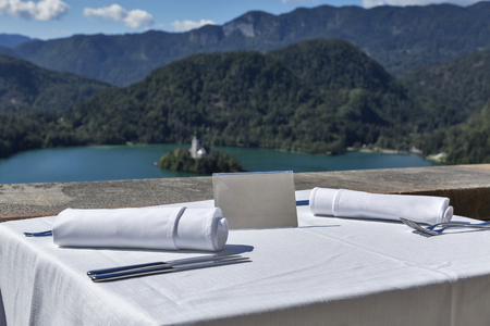 Served table with empty plate outdoor. View over lake Bled, island with church and Alps mountains in the background. Slovenia.
