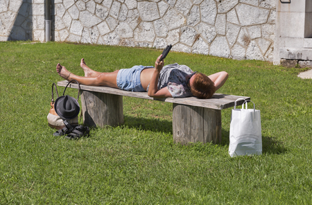 electronic book: tanned middle age caucasian woman in shorts and sunglasses lying after shopping on a bench outdoor and reading electronic book
