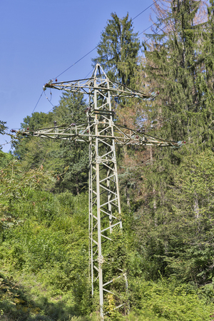 power line tower: high voltage power line tower in the mountain forest with clear sky