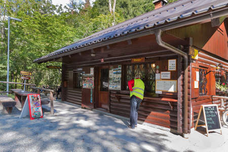 unrecognized: PODHOM, SLOVENIA - SEPTEMBER 08, 2015: Unrecognized service officer stands at the Vintgar gorge ticket office. Vintgar gorge is one of the most popular natural features in Slovenia.