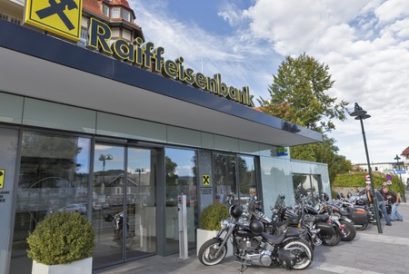 parked bikes: VELDEN, AUSTRIA - SEPTEMBER 08, 2015: People and parked bikes in front of Raiffeisenbank during annual European Bike Week festival. Now it ranks among Europes biggest and best motorcycle events.