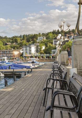 VELDEN, OOSTENRIJK - SEPTEMBER 8, 2015: De mensen lopen langs Worthersee-meerwaterkant met vastgelegde boten. Het is een marktstad in de deelstaat Karinthië, een van de meest populaire vakantieresorts in Oostenrijk. Redactioneel