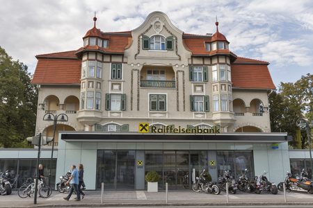 parked bikes: VELDEN, AUSTRIA - SEPTEMBER 08, 2015: People walk in front of Raiffeisenbank and parked bikes during annual European Bike Week festival. Now it ranks among Europes biggest and best motorcycle events. Editorial
